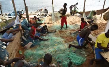 Pescadores de Africa reparando sus redes en Costa de Marfil
